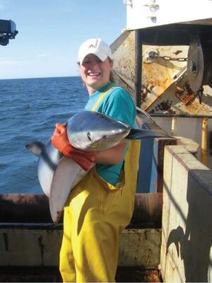 student with oregon reu on boat holding a shark