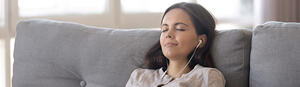 RIO program woman with headphones on couch
