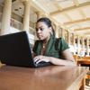 Student studying in library on laptop